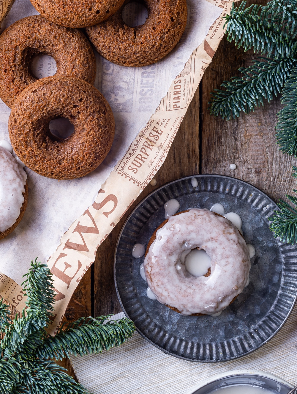 Three plain gingerbread donuts overlapping on a piece of paper. A glazed gingerbread donut is on a plate to the right of the piece of paper. Everything is set on top of a wooden table.