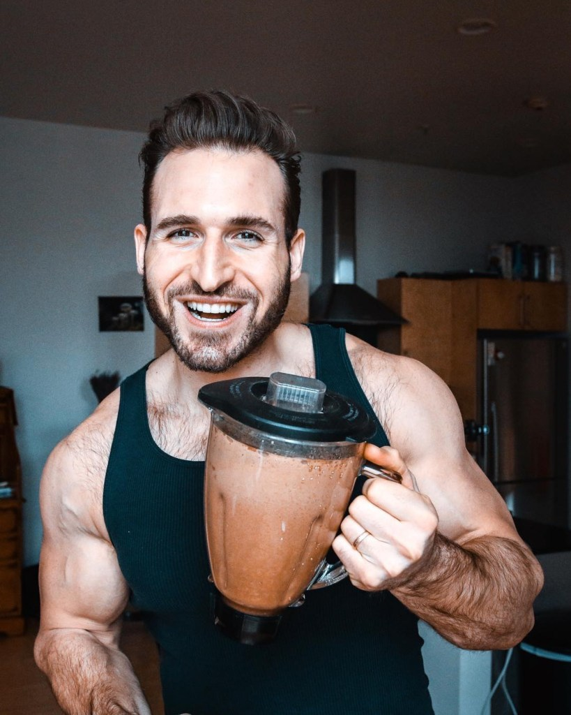 A guy in a black a-shirt holding a blender filled with chocolate protein.