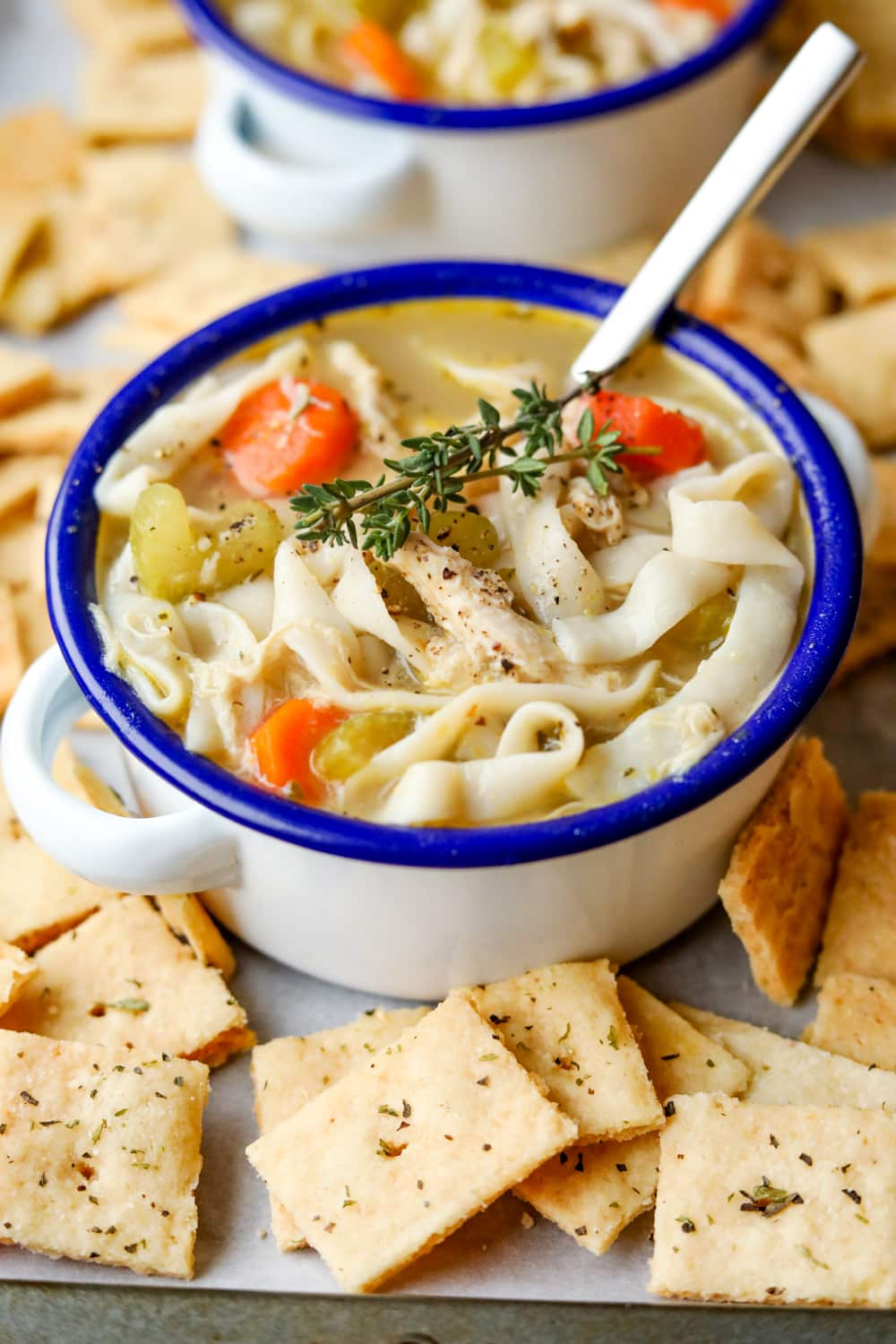 Chicken noodle soup in a white bowl with a blue rim. There are cheese crackers around the bowl, and a spoon in it.