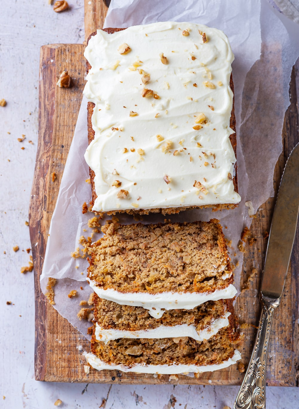 A loaf of carrot cake cutting slices set on top of a cutting board lined with parchment paper.