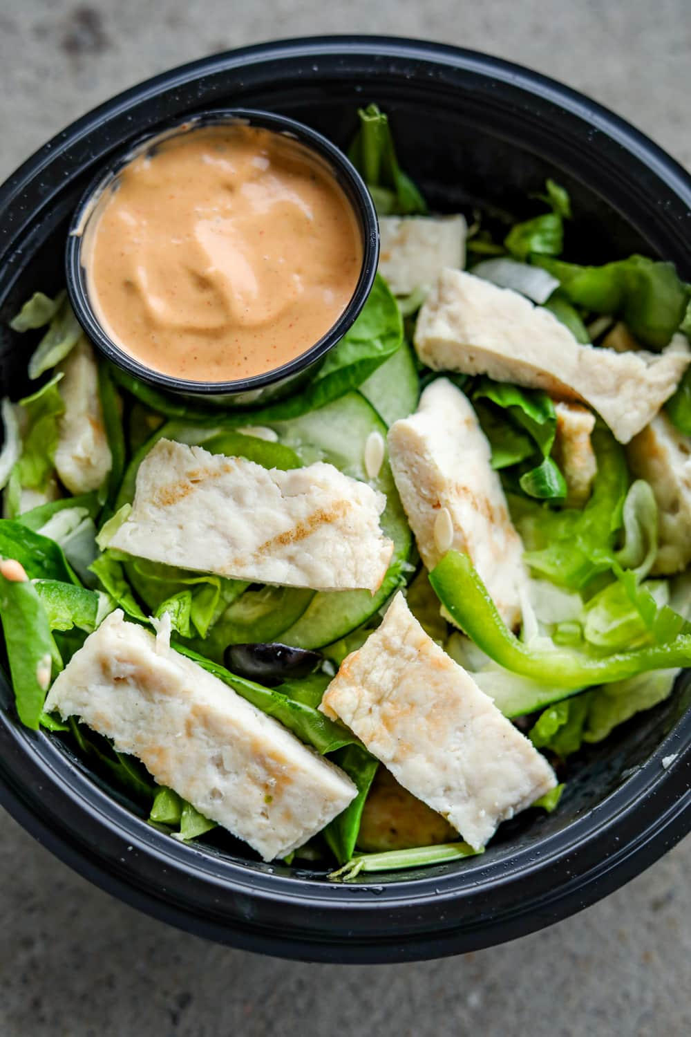 A black bowl filled with vegetables, a cup of orange dipping sauce, and cut up chicken.