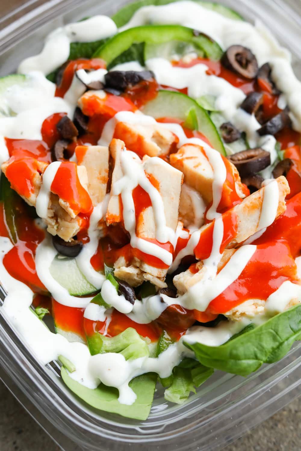 A plastic container filled with green vegetables, black olives, chopped up chicken, and an orange and red sauce.