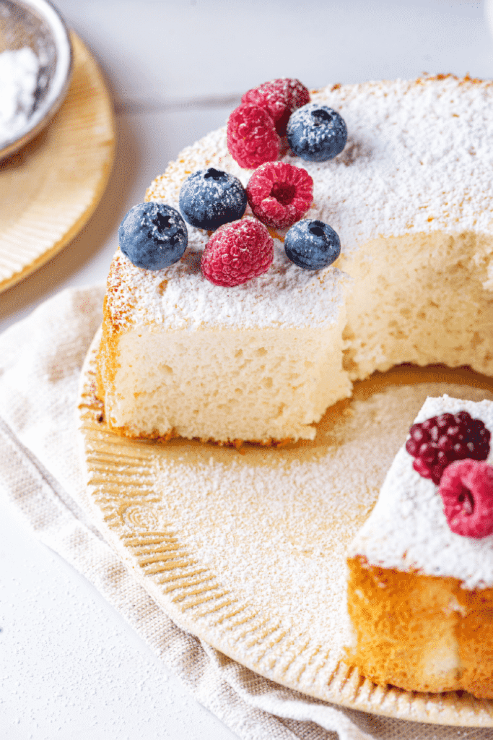 An angel food cake on a plate with a piece cut out of the front of the cake. There are blueberries and raspberries along with powdered sugar on top of the cake.