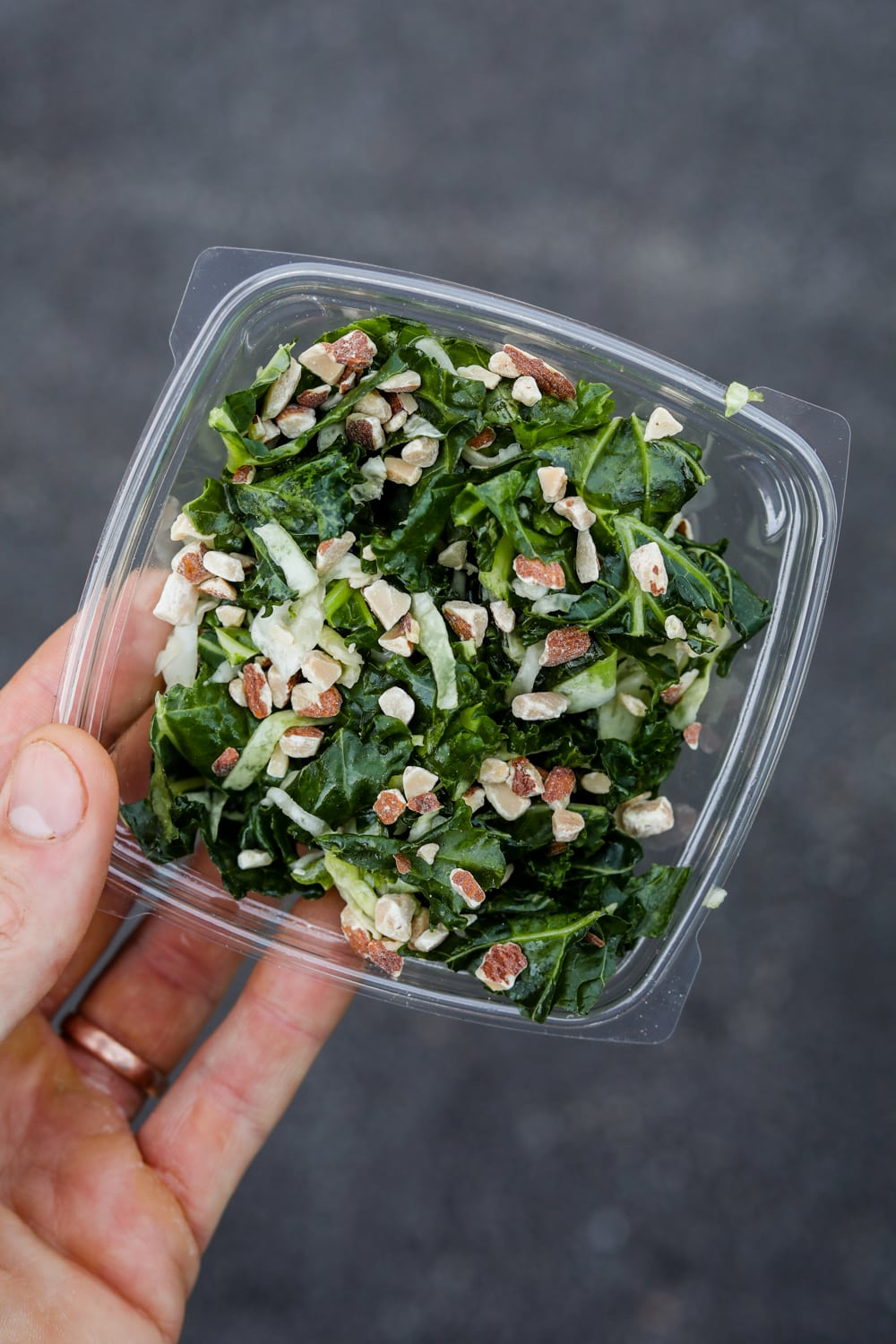 A hand holding a container of kale crunch salad from Chick-fil-A