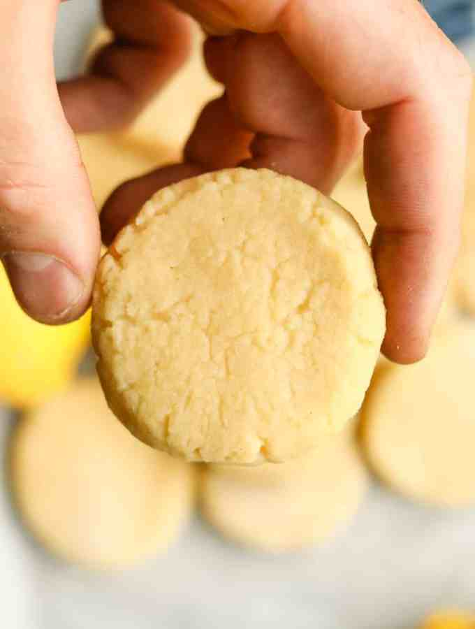 A hand holding a lemon cookie.