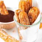Six churros in a glass cup with white parchment paper raft behind them. The glass cup is on a piece of white parchment paper on a plate and there is one churro on the plate with a cup of chocolate sauce behind it.