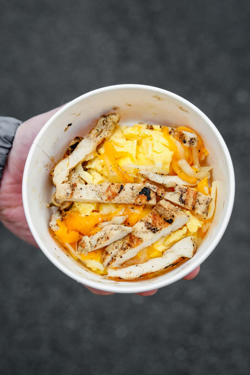 A hand holding a bowl filled with scrambled eggs Monterey and cheddar cheese and grilled chicken strips.