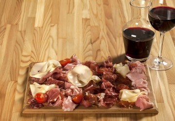 a meat and cheese platter next to some wine