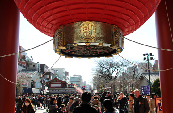 busy street in Japan, filled with people walking, red Japanese lantern overhead