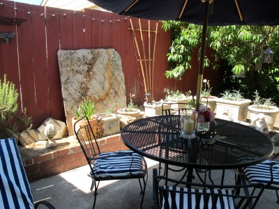 """Our """"found"""" art - leftover slab of granite - against the fence."""