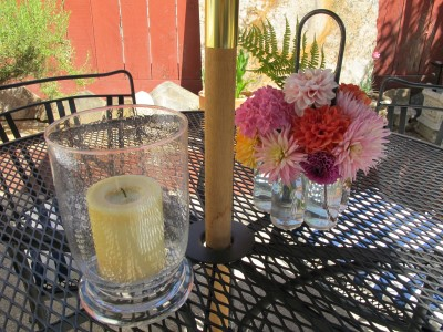 Flowers and candles brighten up any table setting. I liked the bubbled texture of the hurricane glass, which makes the candlelight dance. I found this wonderful iron stand holding a circle of fused glass bottles, which make it easy to create a bouquet that spilleth over, from Flowerland.