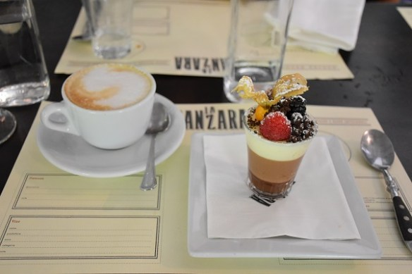 Latte and chocolate dessert with fruit dusted in sugar.