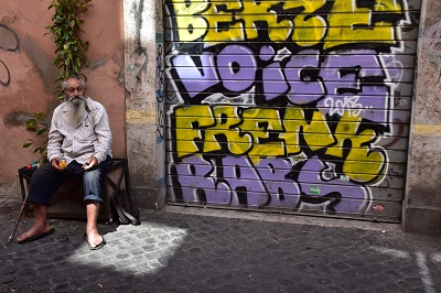 Yes, David gave change to this homeless man to take his photograph by colorful graffiti.