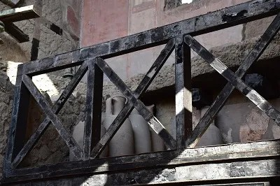 Charred but intact wooden balcony. Archaeologists found many wooden doors, door frames, window frames, and other wooden building elements throughout Herculaneum.
