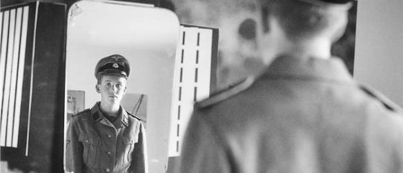 A still from 100 Clocks - Hanna's brother trying on their grandfather's uniform - from the IDFA Festival site.