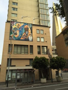 The I Hotel mural with the TransAmerica Pyramid in the background.