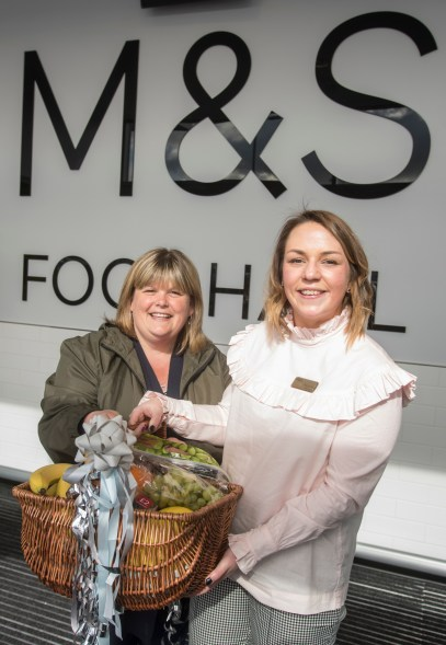 M&S store manager Alyson Crombie presents first customer Sharon Duncan with a fruit basket
