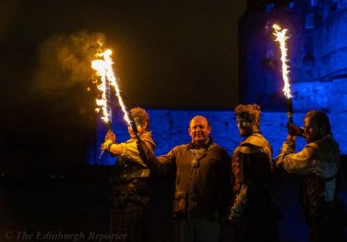 Four men with fiery swords in front of blue castle