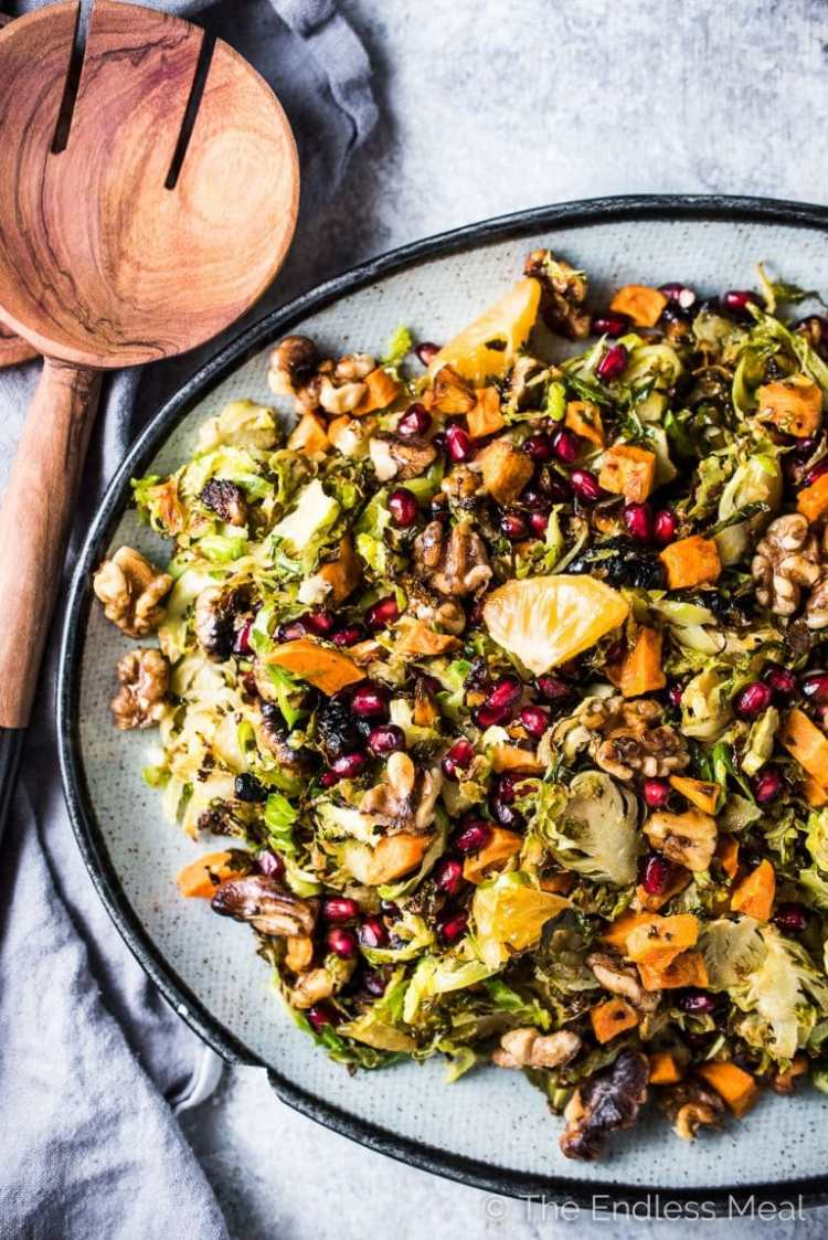This delicious Shaved Brussels Sprout Salad has all of your favorite autumn flavors. The Brussels are first roasted and then tossed in an orange lemon vinaigrette. You'll find sweet potatoes, toasted walnuts, mandarin oranges, and pomegranate all hiding in this healthy and delicious side dish. It would be perfect on your Thanksgiving or Christmas table and delicious all winter long. Whole30 + paleo + easily made vegan.  | theendlessmeal.com