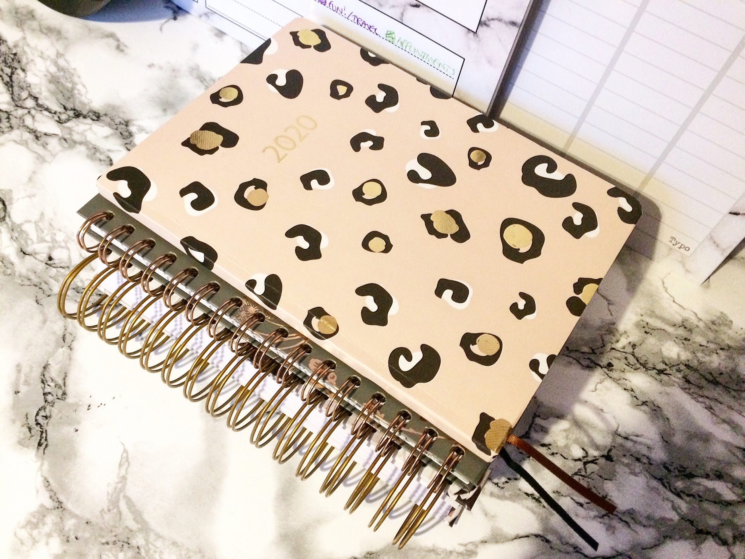 A pink leopard print 2020 diary on a marble desk.