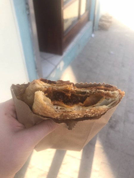 A chicken and chocolate empanada wrapped in a brown paper bag with a bite taken out of it being held in a hand