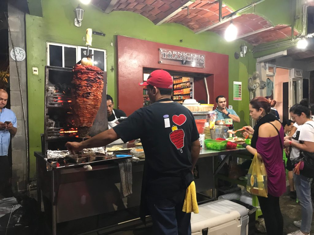 A street taco stand surrounded by people. There is a large spit of slow roasting pork with a pineapple on top of the spit.