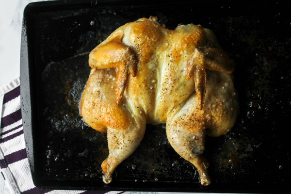 Roasted Chicken on a weathered baking sheet sprinkled with coarse salt