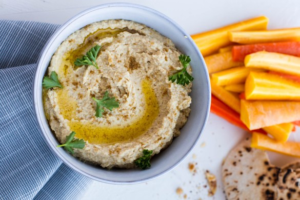 Hummus topped with olive oil and parsley beside a pile of sliced carrots