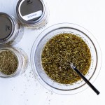 Dried herbs combined with olive oil, vinegar, shallots and garlic for s simple marinade beside jars of dried herbs