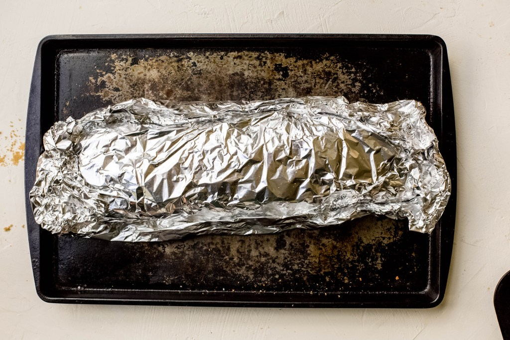 A baking sheet with a foil pack containing oven baked ribs