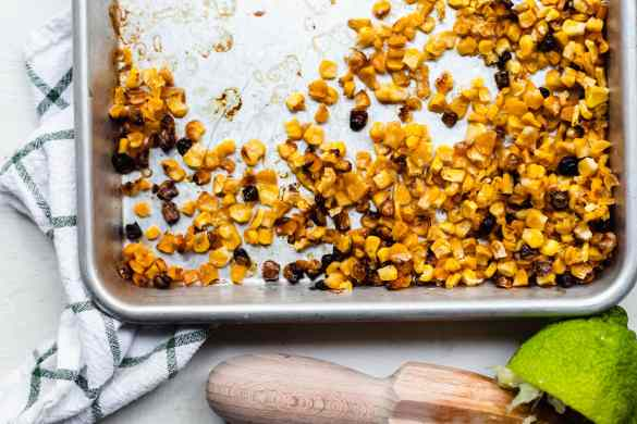 A sheet pan with roasted corn piled in the corner. A citrus juice and half a lime discarded below the sheet pan.