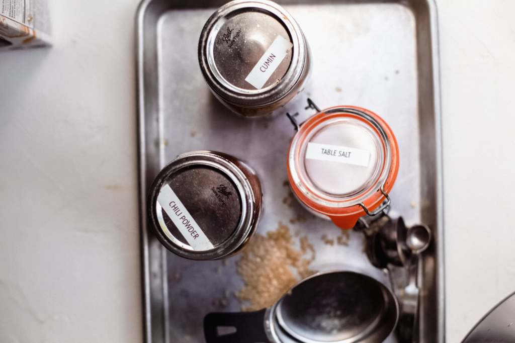 Jars of cumin, chili powder, salt all on a baking sheet next to a set of measuring spoons and a one cup measuring cup.