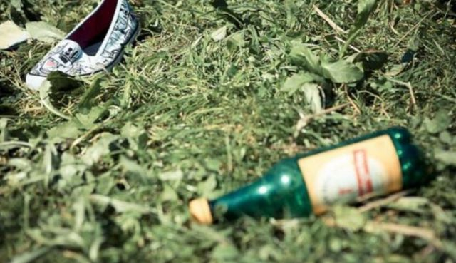 An empty bottle of alcohol and a stray slipper on grass