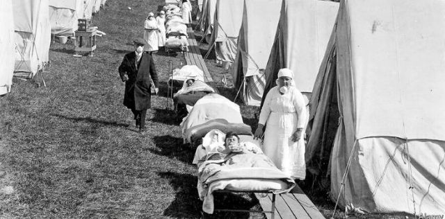 Nurses assisting sick people outside tents in the outdoors
