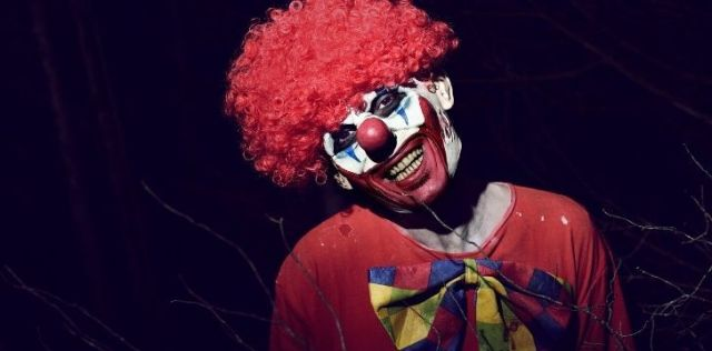 A scary clown in a blood red wig