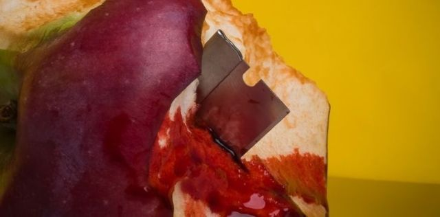 A sharp razor blade inside a half eaten apple dripping in blood