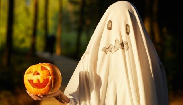 A Halloween costume made of a white bed sheet