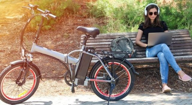 An electric bike with a woman working on a bench next to it