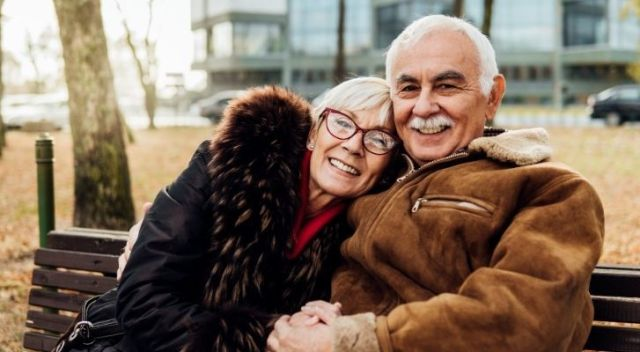 An older couple hugging and looking happy and relaxed