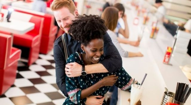 A young couple hugging at a diner