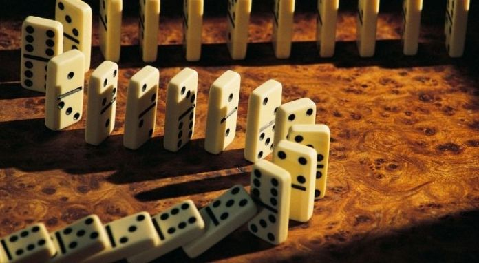 Stacked dominos tumbling over