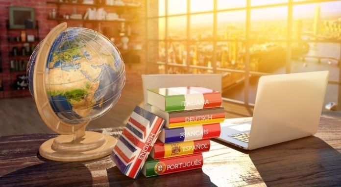 A globe, laptop and several books on languages