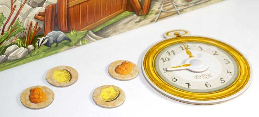 Cardboard clock with movable hand pointing at the 9. Gold nugget tokens are scattered nearby.