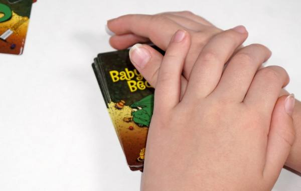 Two hands covering a small deck of Baby Dragon Bedtime cards