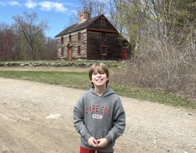Boy standing in front of a historical building on a dirt trail