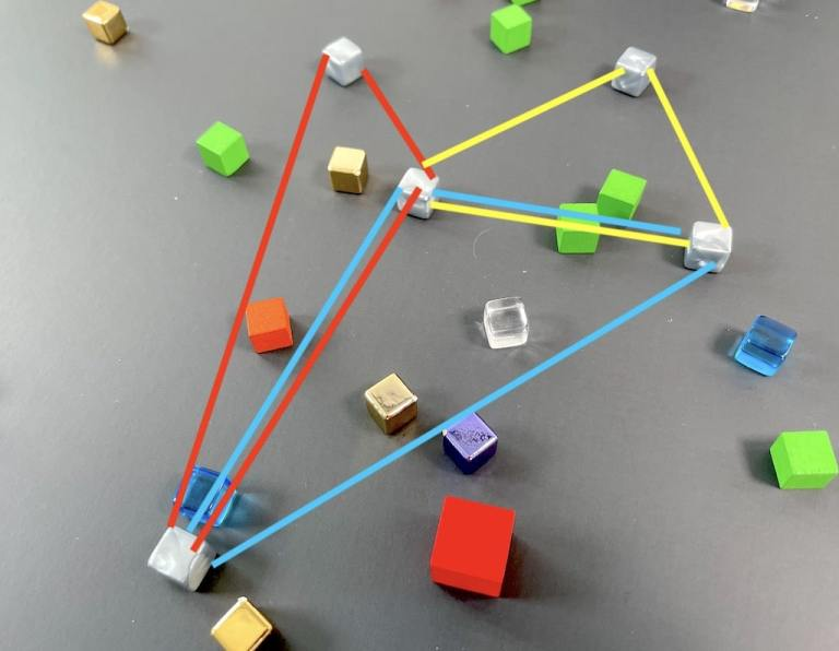 A scattering of cubes on a black background. Three triangles are overlaid on the image, in red, yellow, and blue.