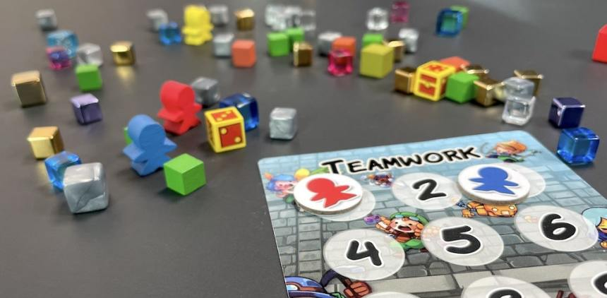 Cubes scattered across a dark surface. Blue and red meeple side by side, yellow meeple in the distance. Card in foreground labeled Teamwork with a red marker on the first spot and a blue marker on the third spot.