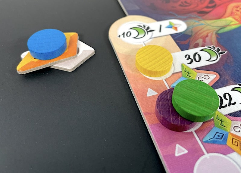 A blue token with two cardboard star fragments underneath. It's next to a track with other color tokens; the last slot in the track indicates 10 more points per star.