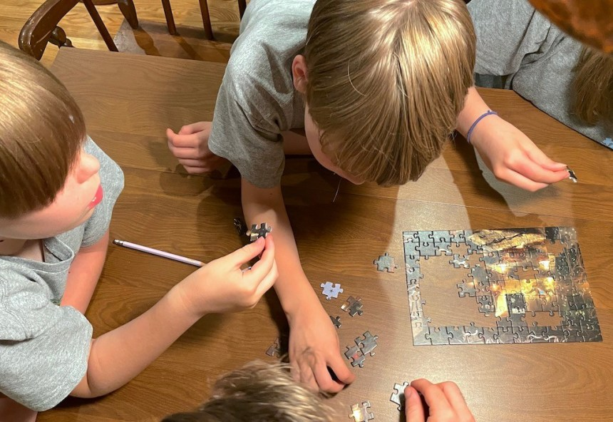 Children working on a jigsaw puzzle from EXIT: The Sacred Temple
