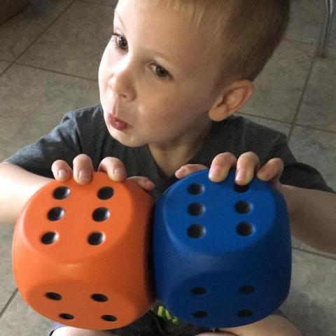boy holding large dice